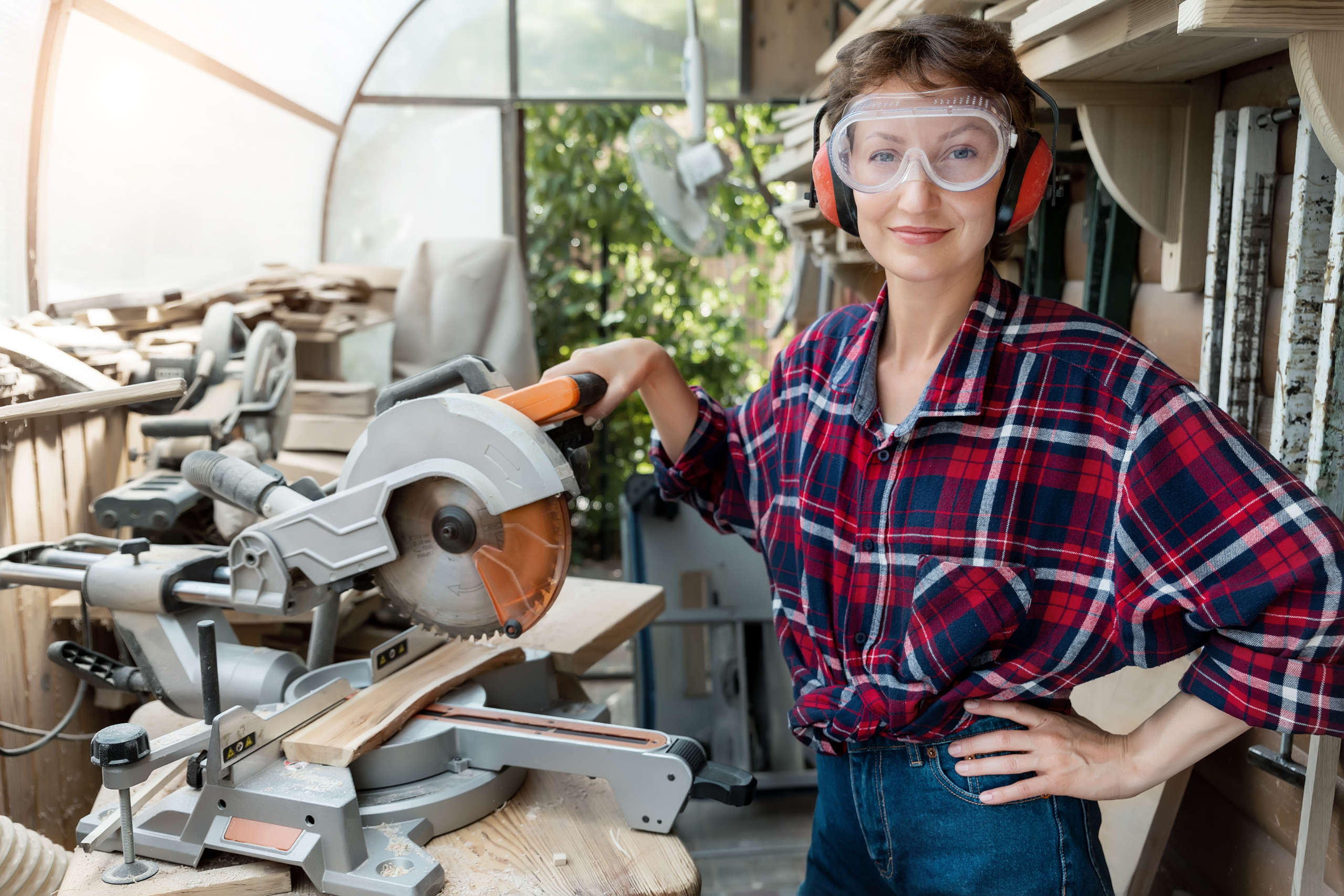 confident woman in safety goggles with saw
