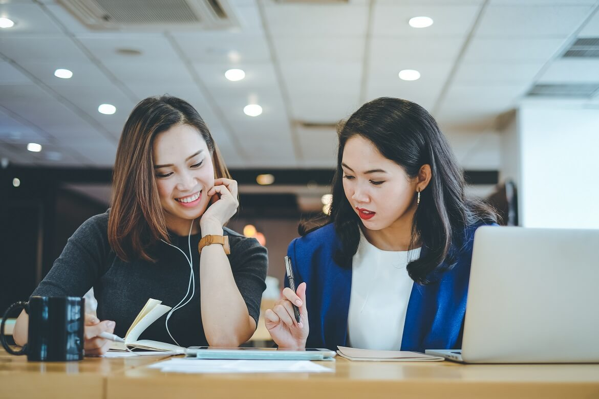 two asian businesswomen meeting and discussing about working process at the office business concept