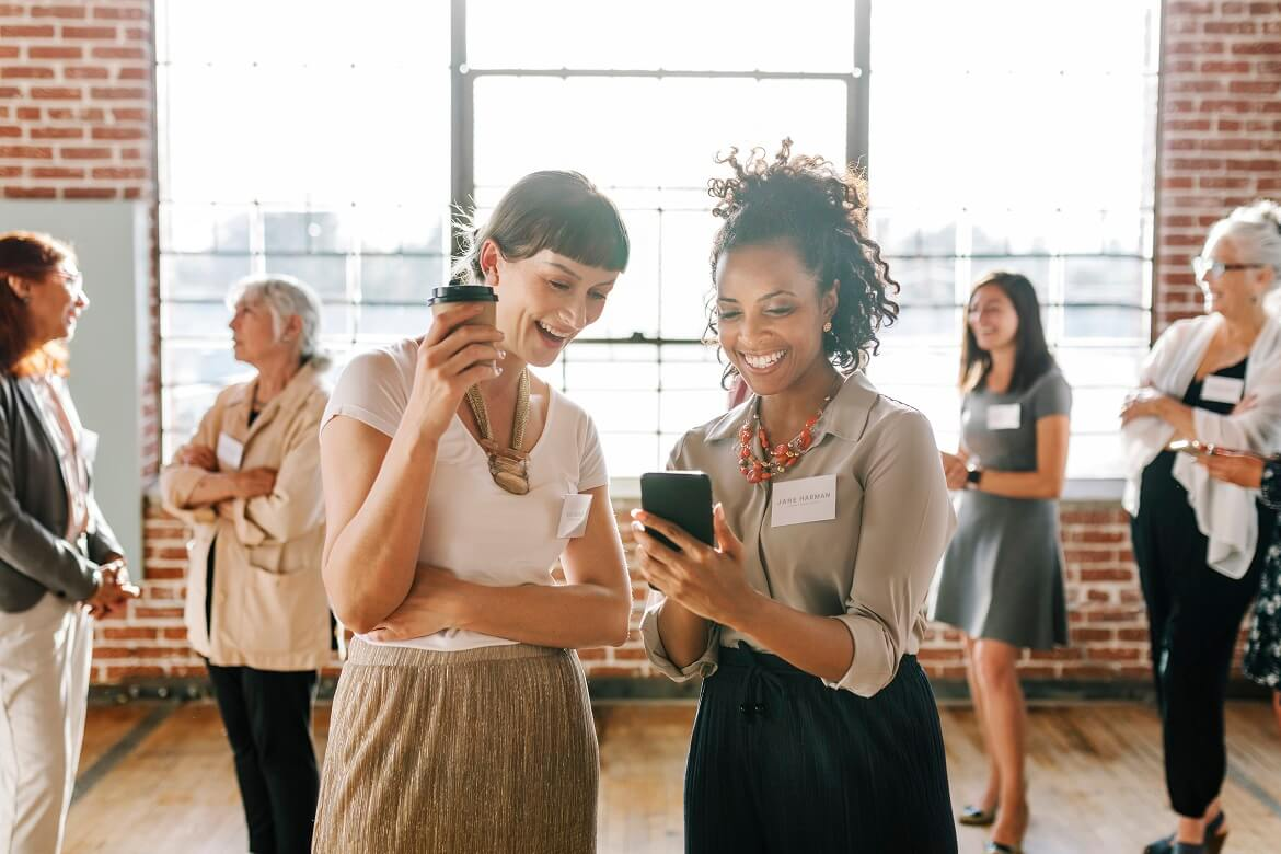 female coworkers looking at a smartphone