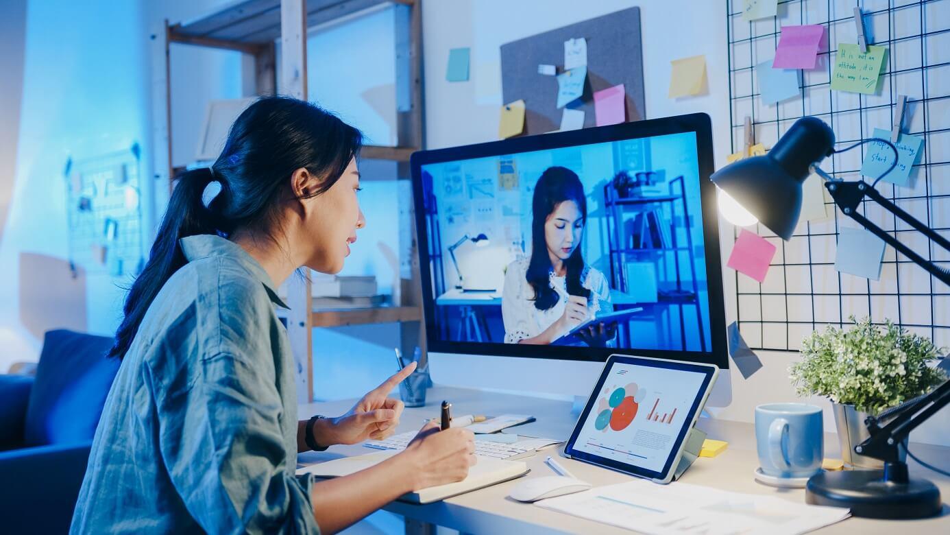 female businesswoman using desktop to speak with colleague