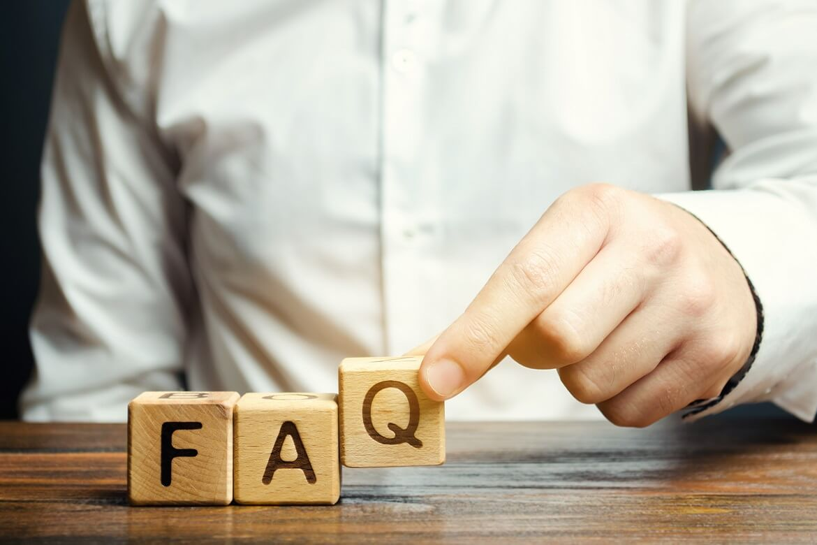 """male employee uses wooden blocks to form the word """"faq"""""""