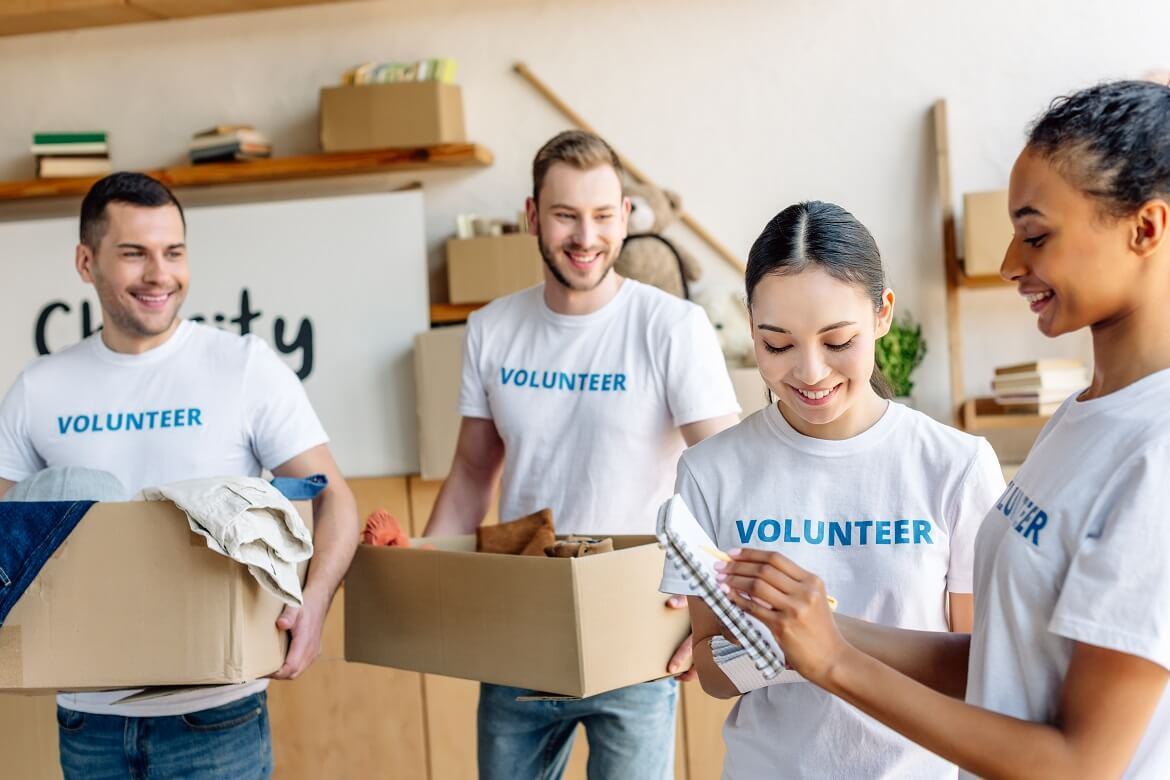 diverse group of four young volunteers in white t-shirts moving boxes