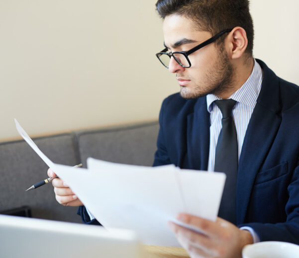 business man in glasses reading resume