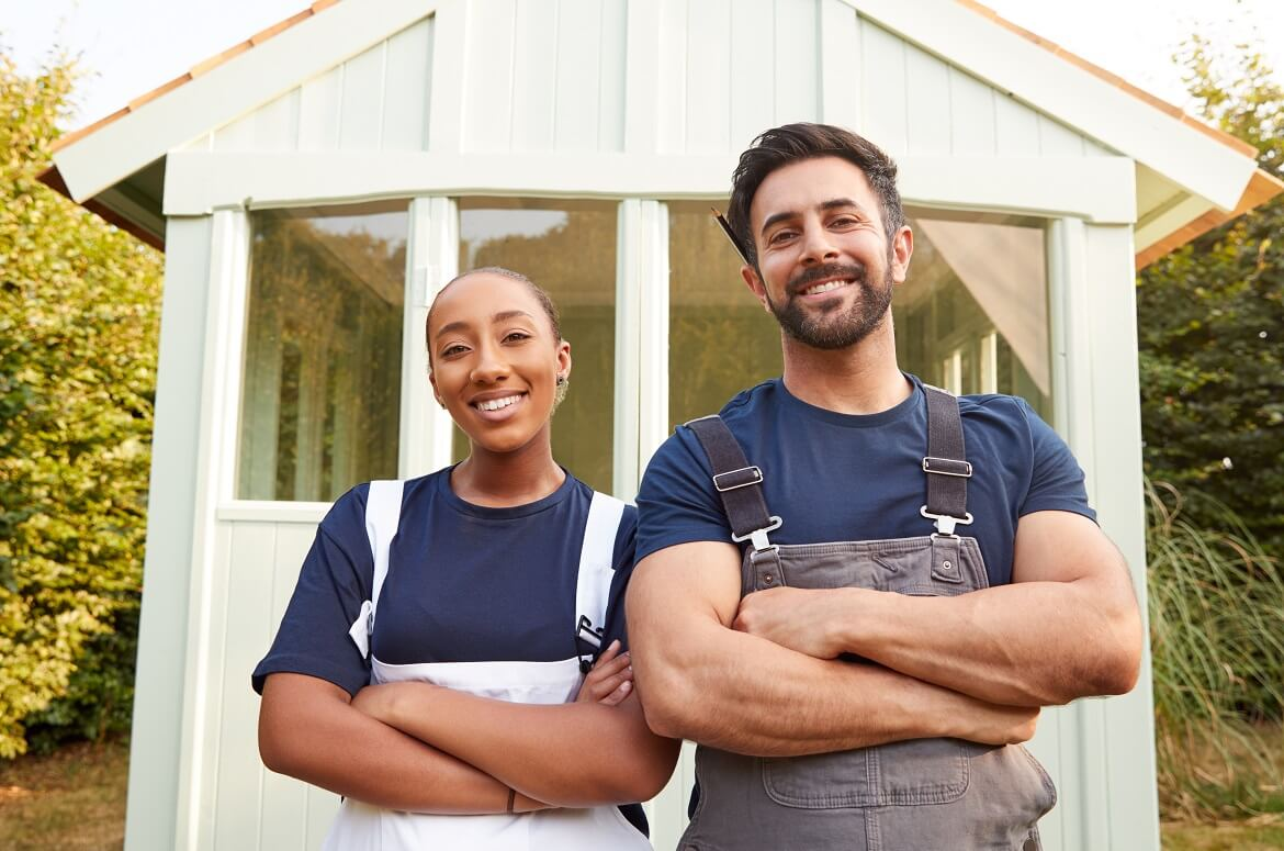 male carpenter with female apprentice standing in front of finished outdoor summerhouse