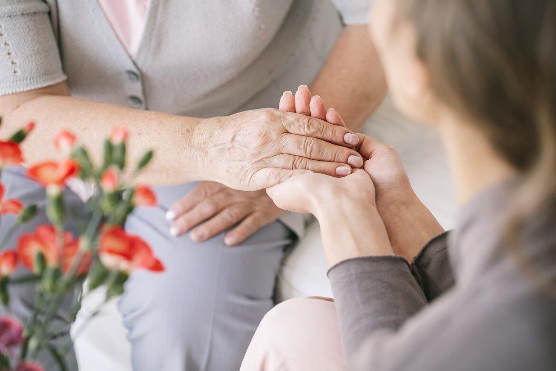 caretaker giving her hand