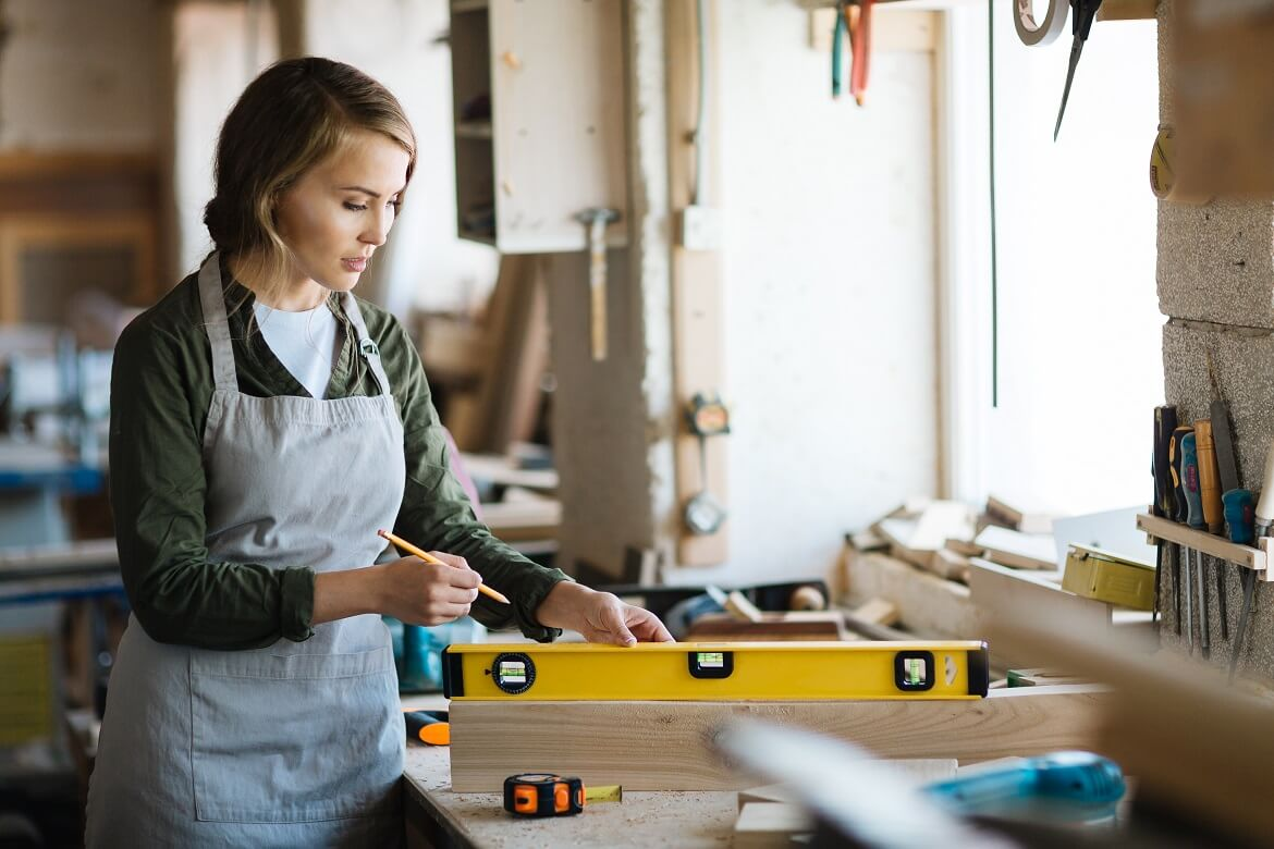 female carpenter using a leveler on a piece of wood and holding a pencil