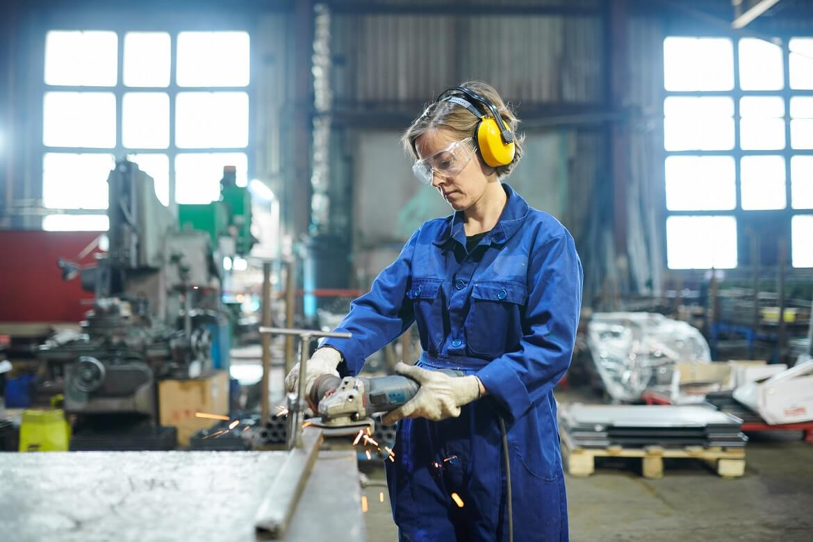 woman wearing safety goggles and earmuffs while working in garage