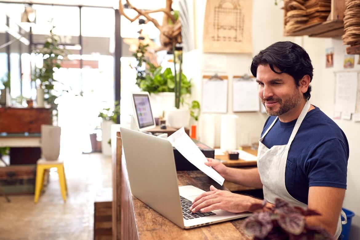 male sales assistant working on laptop behind sale