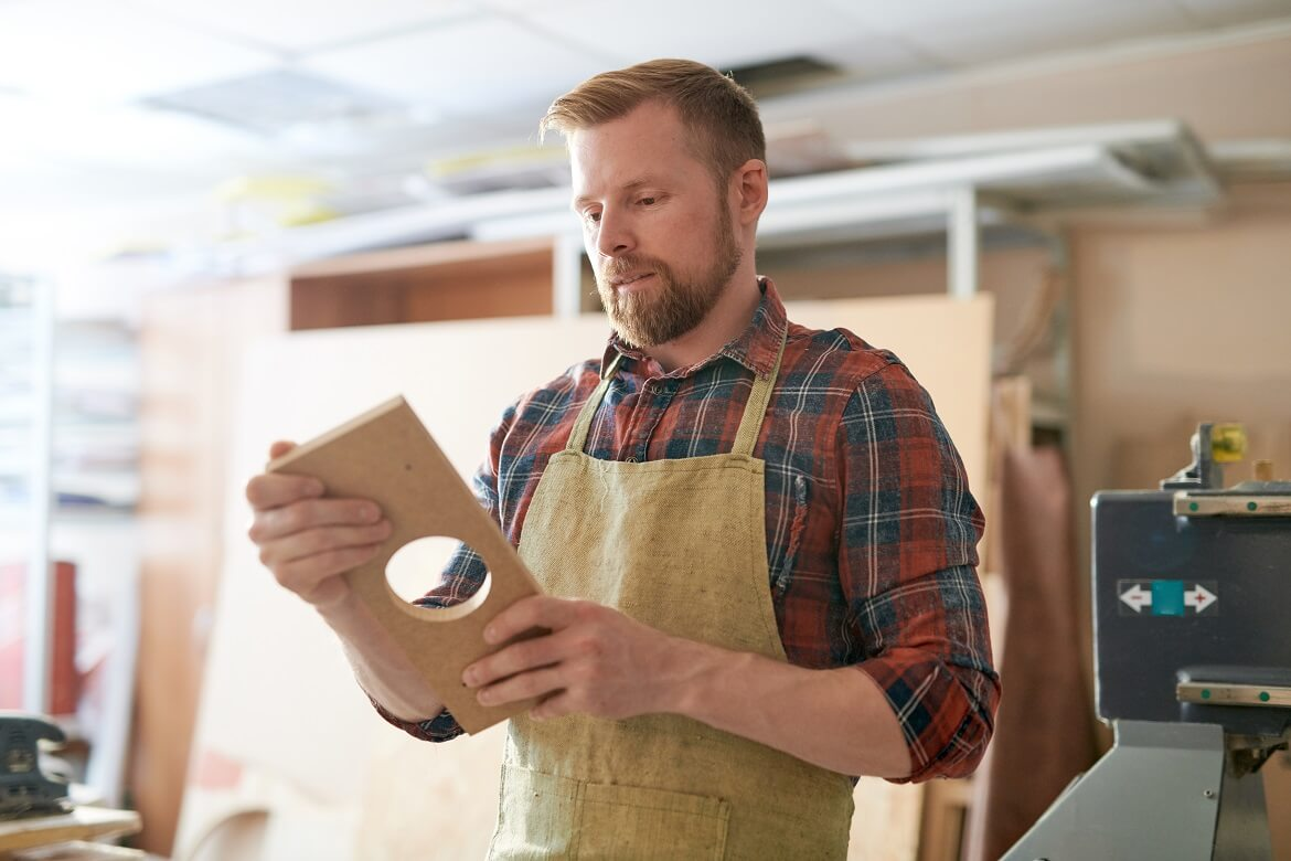 woodworker holding a piece of wood