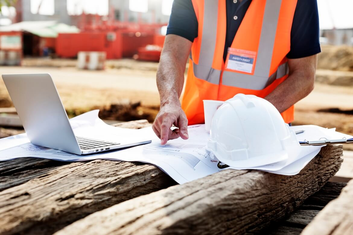 Closeup of contractor in construction site pointing at plan on wooden sleeper