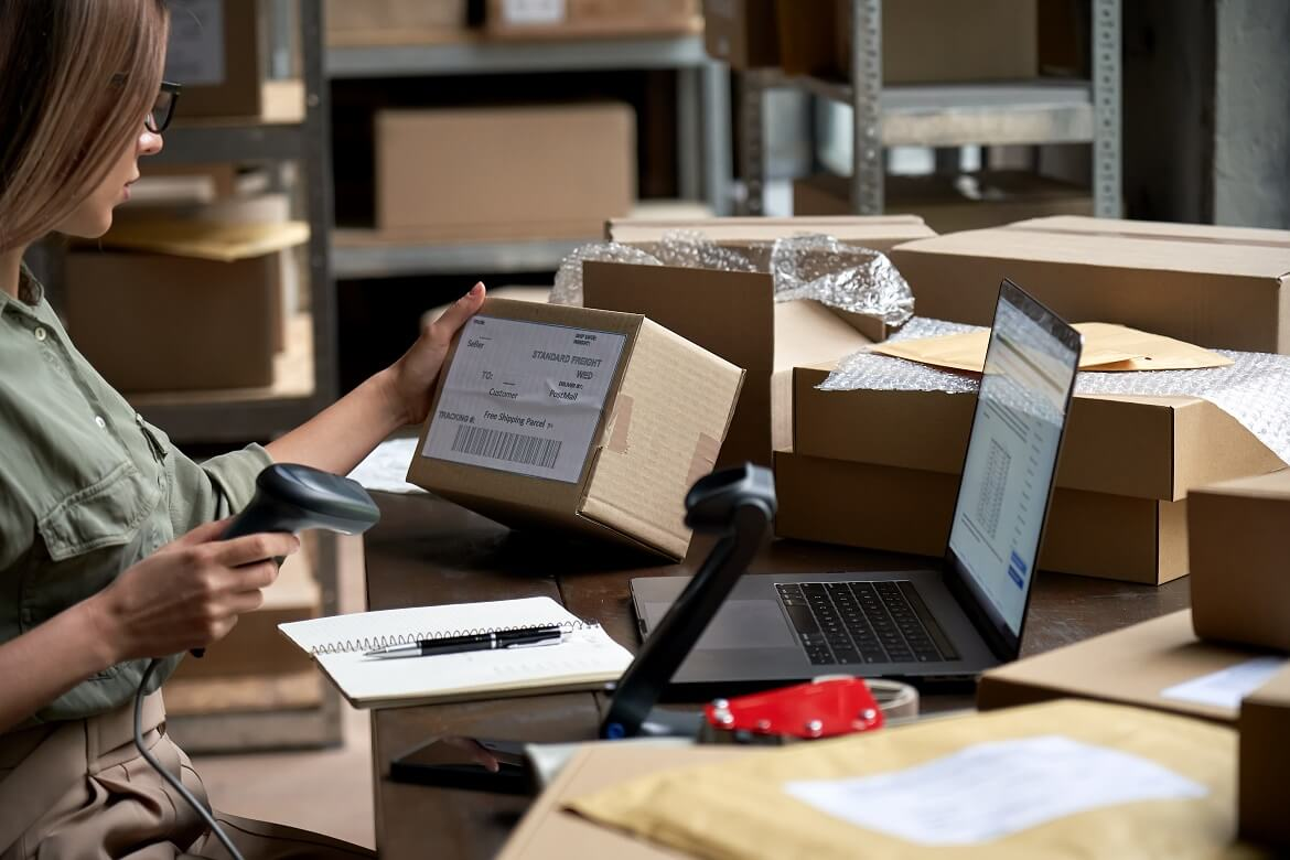 Female seller scanning ecommerce shipping box in dropshipping warehouse